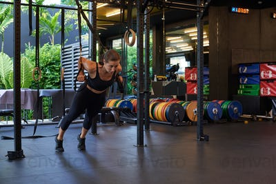 Strong and slim sportswoman doing workout alone in gym in daytime