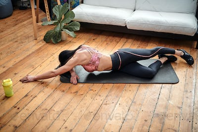 Peaceful portrait of a sportive woman she lying on mat at home