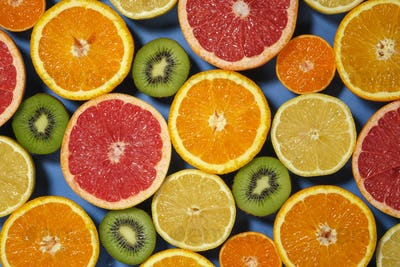 Assortment of various cut raw fruits on blue background, full frame.