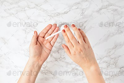 Woman disinfecting hands with hand sanitizer gel with alcohol. Protection against viruses and