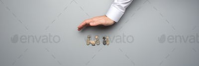 Wide view image of male hand making protective gesture over a family made of pebbles