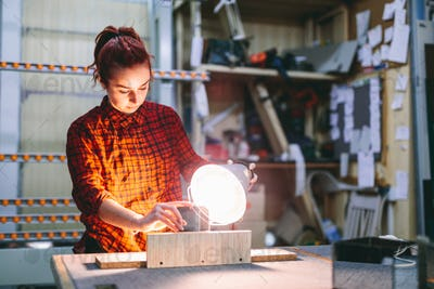 Woman glazier worker sticking together glass panes with ultraviolet lamp
