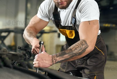Male mechanic with muscular hands and tattoo repairing auto