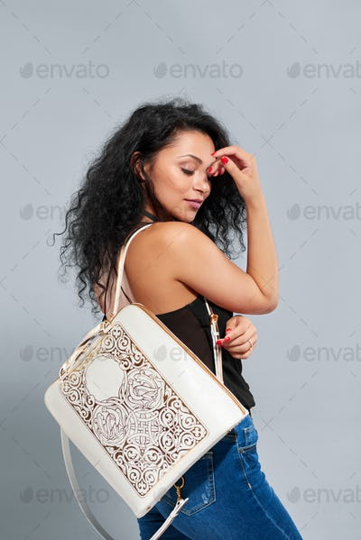 Wonderful girl with black curly hair carries white and gold backpack