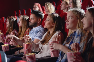 Group of female watching comedy in cinema