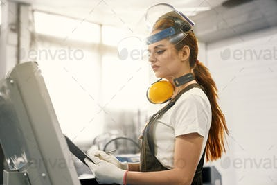 Woman engineer working on factory with computerized machine