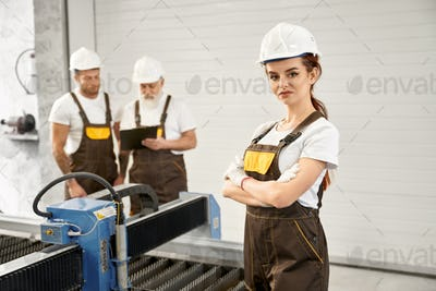 Woman engineer posing with workers on metalworking factory