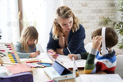Young mother helping children during making homework