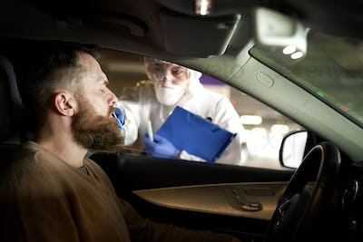 Medical worker performing drive-thru COVID-19 test