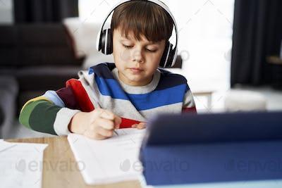 Schoolboy in headphone during homeschooling