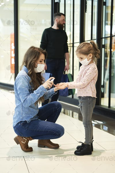 Mom disinfects her daughter's hands while shopping at the mall
