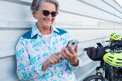 Portrait of attractive and smiling senior woman using mobile phone, standing close to her bicycle