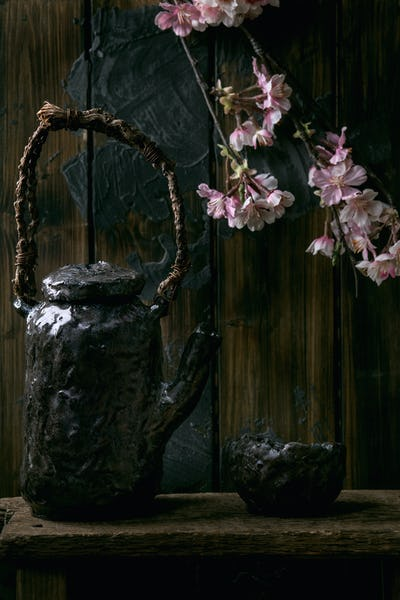 Tea drinking ceramic cup and teapot with blooming cherry branches