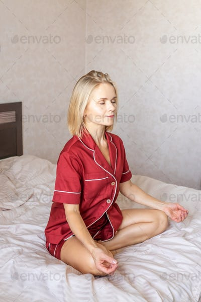 Woman sits in peaceful posture on bed.