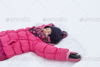 Little girl in a pink jacket and hat lies in the snow copy space.