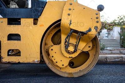 Close up on the road roller working on the new road construction site.