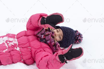 A warmly dressed little girl lies in the snow close up.