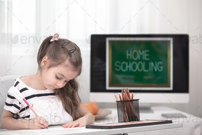 The girl is sitting at the table and doing homework. The child learns at home. Home schooling.