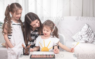Mother with children sitting at the table and doing homework.