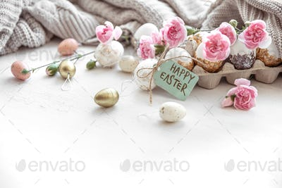 Festive easter composition with eggs, flowers and easter decor details.