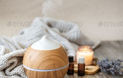Cozy composition with an air humidifier, a set of aromatic oils and a candle.
