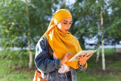 Arab woman student. Beautiful muslim female student wearing bright yellow hijab holding tablet.