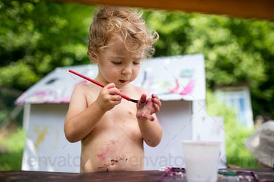 Topless small blond girl painting paper house outdoors in summer