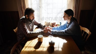 Portrait of sad poor mature couple indoors at home, poverty concept