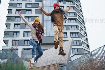 Cheerful young couple owners jumping outdoors in front of new flat, new home and relocation concept
