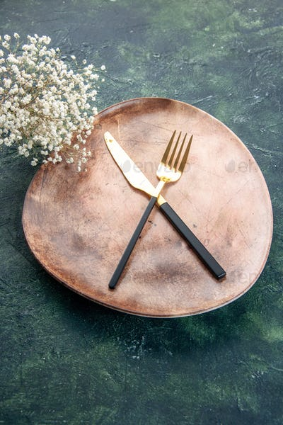 front view unusual brown plate with golden fork and knife on dark blue background meal utencil