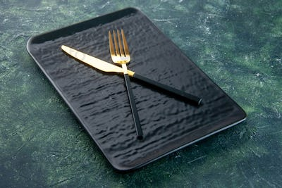 front view black plate with golden knife and fork on dark blue background utencil color cutlery
