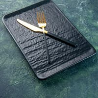 front view black plate with golden knife and fork on dark blue background utencil color dinner