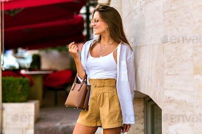 Outdoor full length portrait of stunning slim tanned brunette model