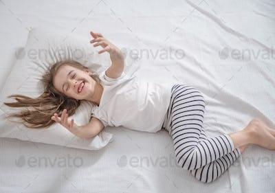 Cute little girl in bed woke up in the morning .