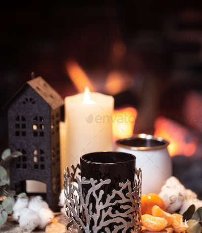 Cozy composition with a cup, candle and tangerines on a blurred background.