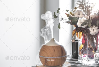 Modern oil aroma diffuser in the living room on the table copy space.