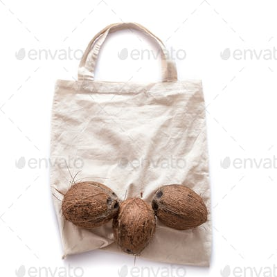 Zero waste and plastic free concept. Coconut on eco bag over white background. Flat lay. Copy space.