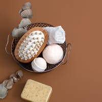 Spa composition with bath accessories in a basket on brown background.