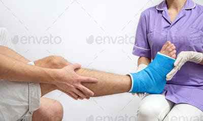 Female doctor in a blue medical gown checking broken leg on male patient.