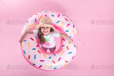 A little child girl lying on a donut inflatable circle. Pink background. Top view. Summer concept.