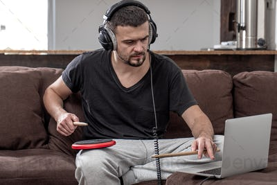 A young man with headphones learns to play the drum using online lessons.