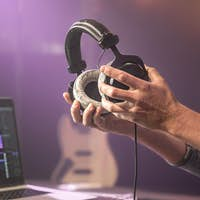 Studio audio headphones for recording sound in male hands on a blurred studio background.