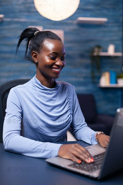 Cheerful african woman speaking in the course of video call