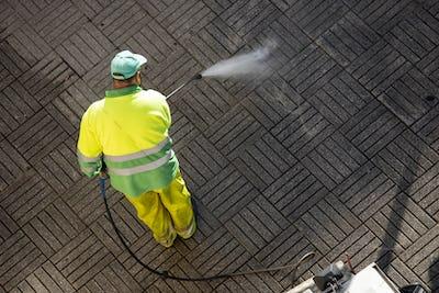 Worker cleaning a street sidewalk with high pressure water jet machine