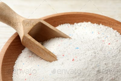 Bowl with washing powder and scoop, close up