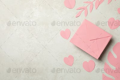 Envelope, paper leaves and hearts on white textured background