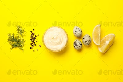 Bowl with mayonnaise and ingredients on yellow background, top view
