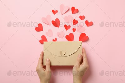 Female hands hold envelope on pink background with decorative hearts