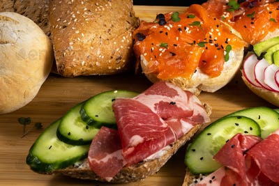 An assortment of sandwiches with fish, cheese, meat and vegetables lay on the board and a bun