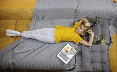 Girl lying on the bed, enjoying sweet cookies and dreaming, digital detox, slow living, top view
